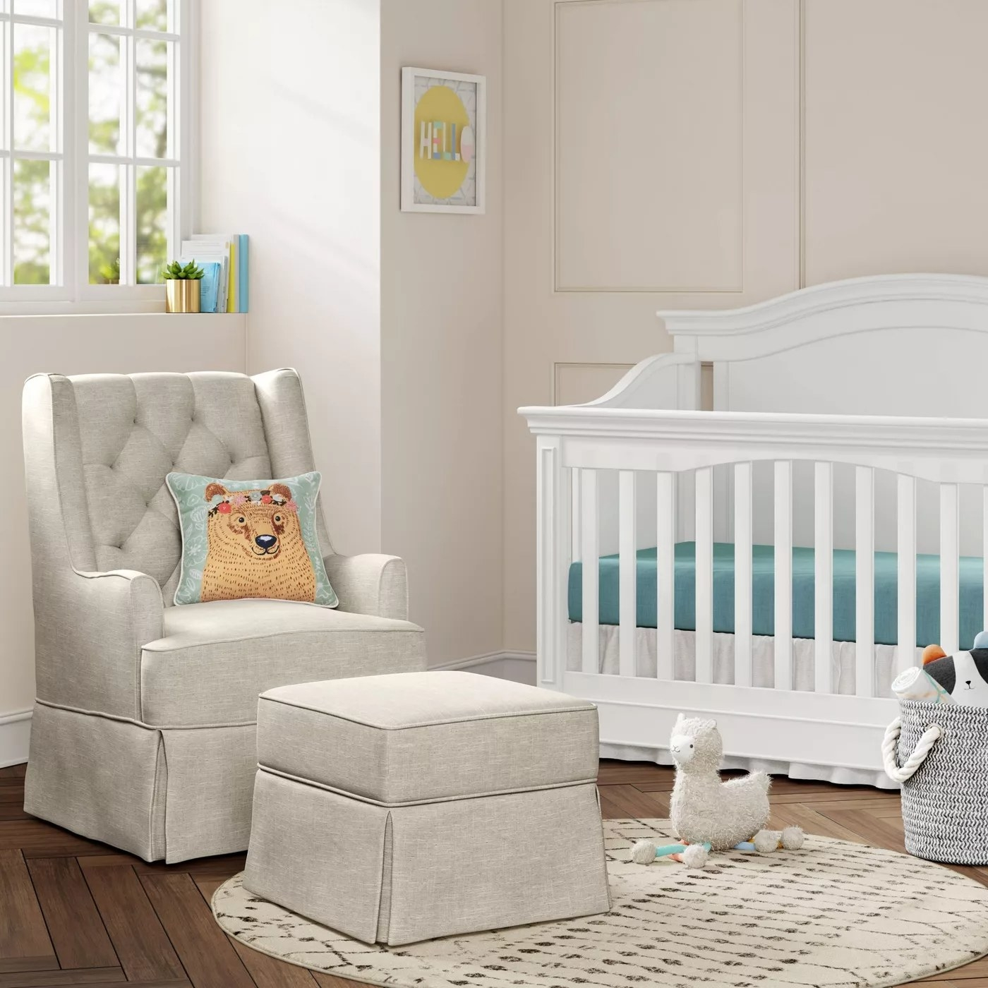 The tufted beige glider with the matching ottoman in front of it in a nursery