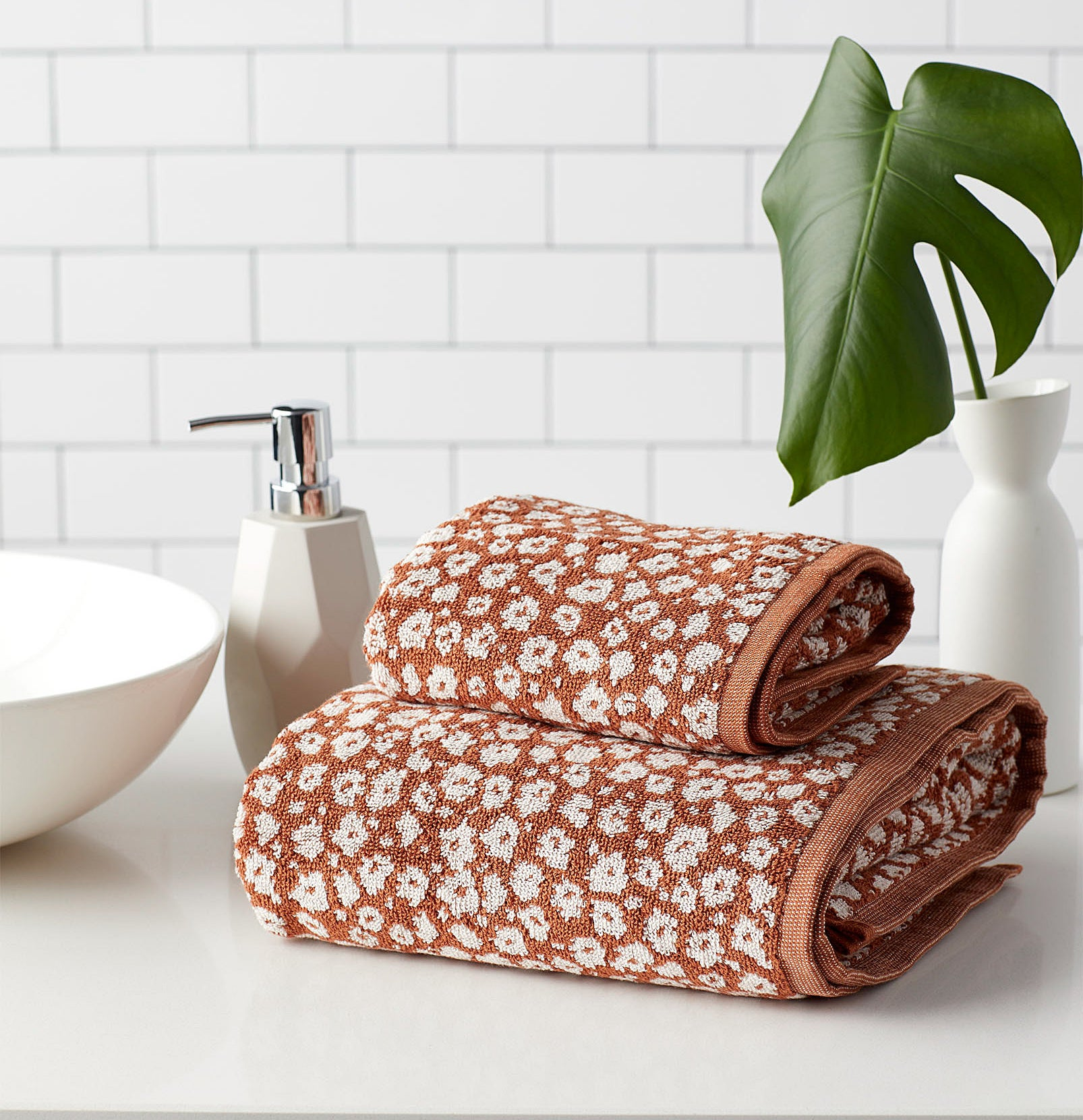 Two towels (one hand and one bath) stacked together in a clean bathroom