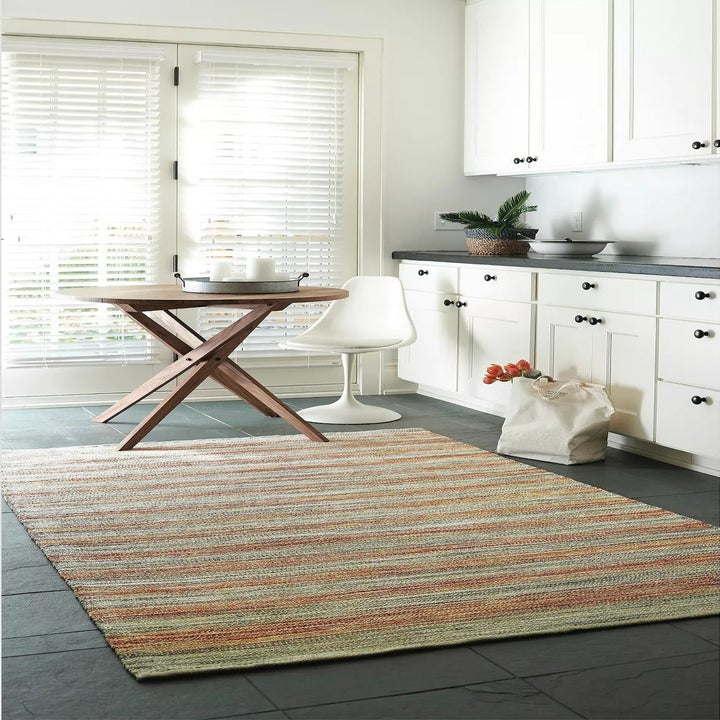 The beige rug with red and orange stripes woven in