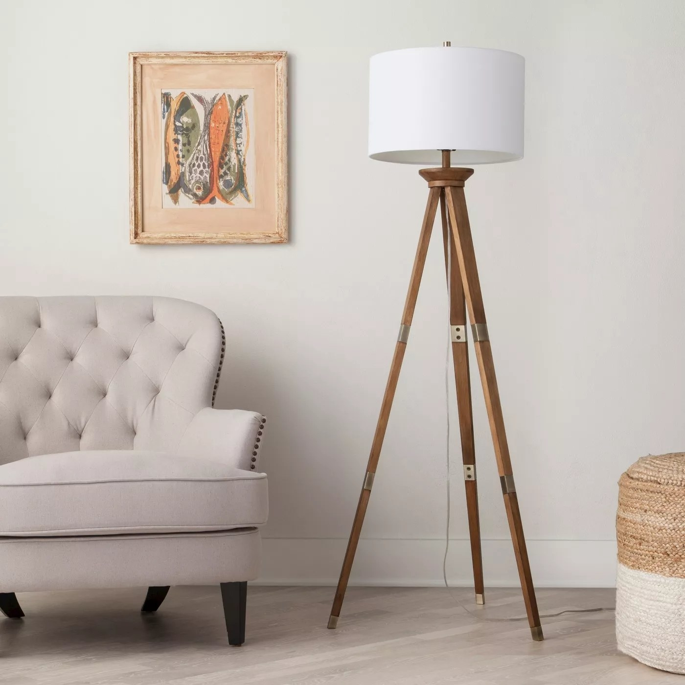 The tripod lamp with a round white lamp shade in a living room