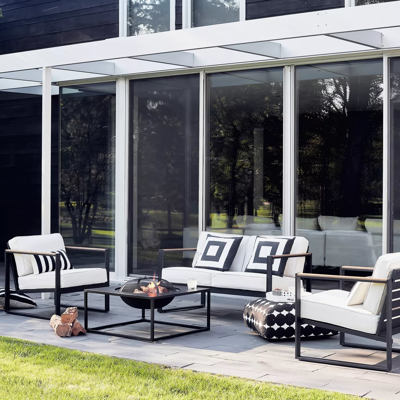 The loveseat with a black metal frame in a backyard with two matching chairs on either side