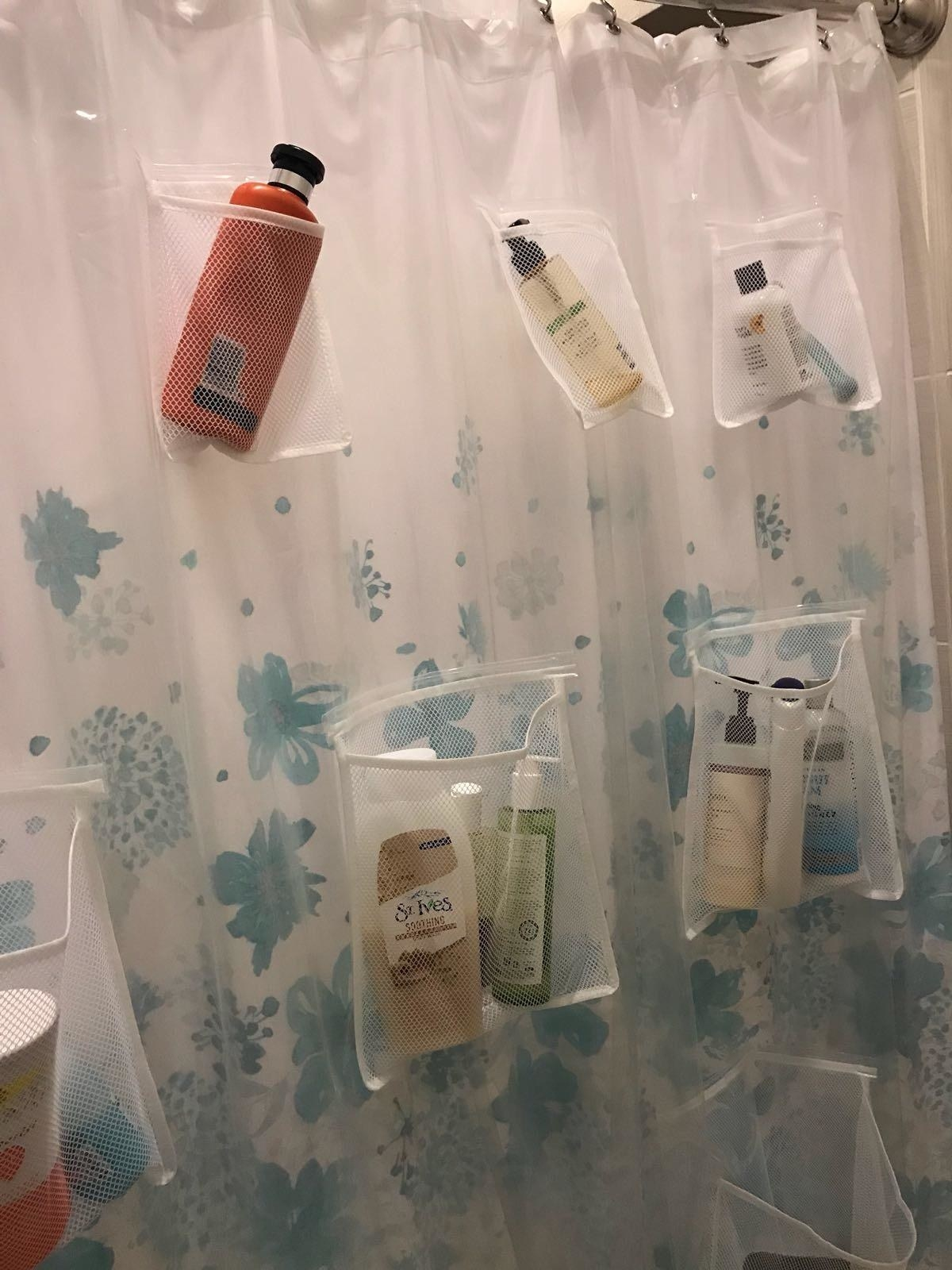 reviewer photo showing the shower curtain with bath products in the pockets