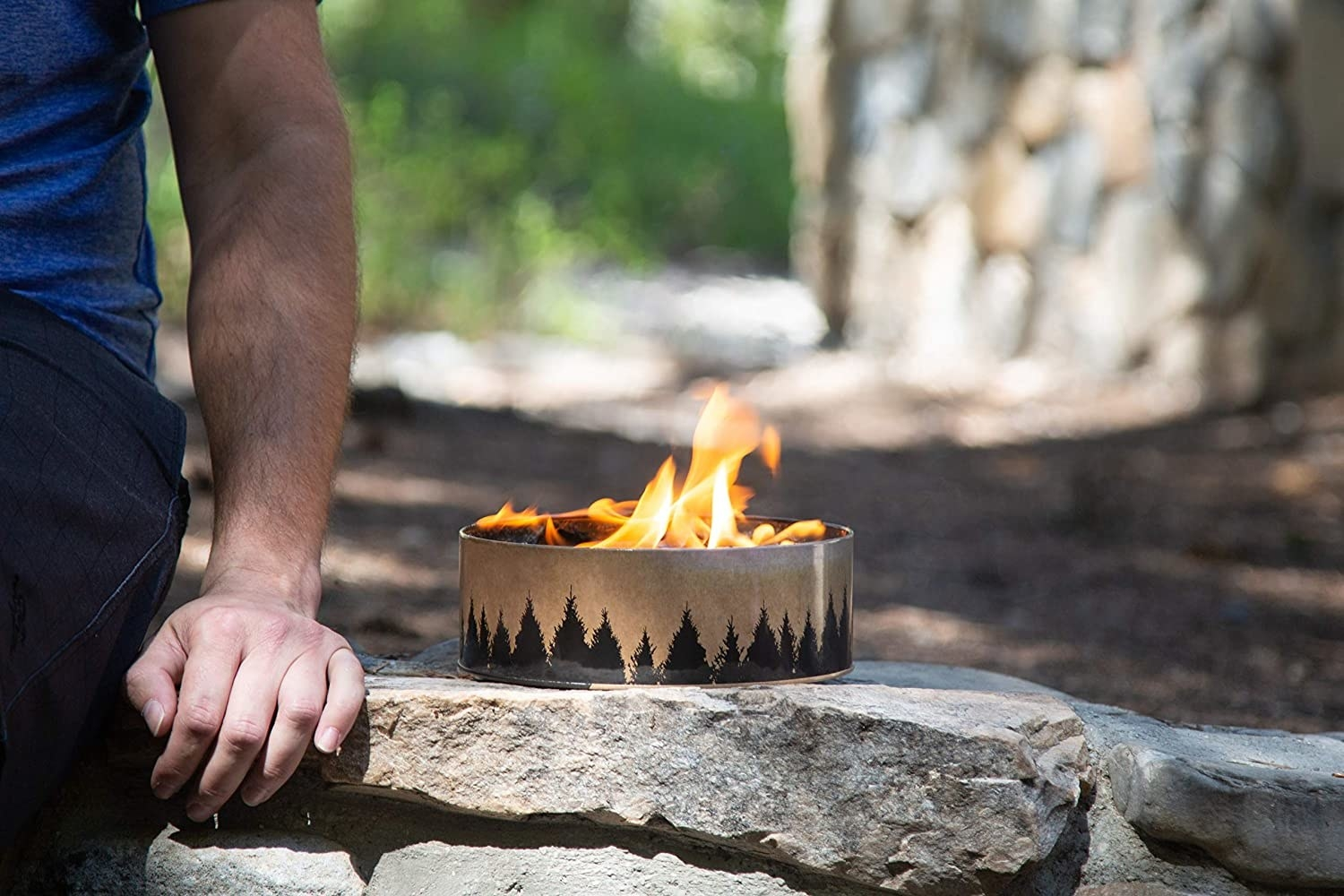 A person sitting next to the circular mini fireplace