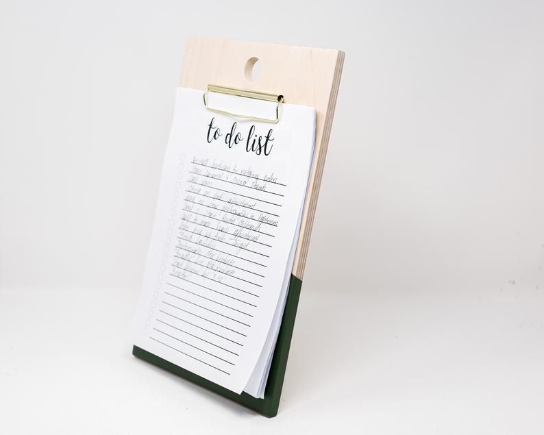 The rectangle-shaped clipboard with light brown on the top and green on the bottom with a clip and paper in it