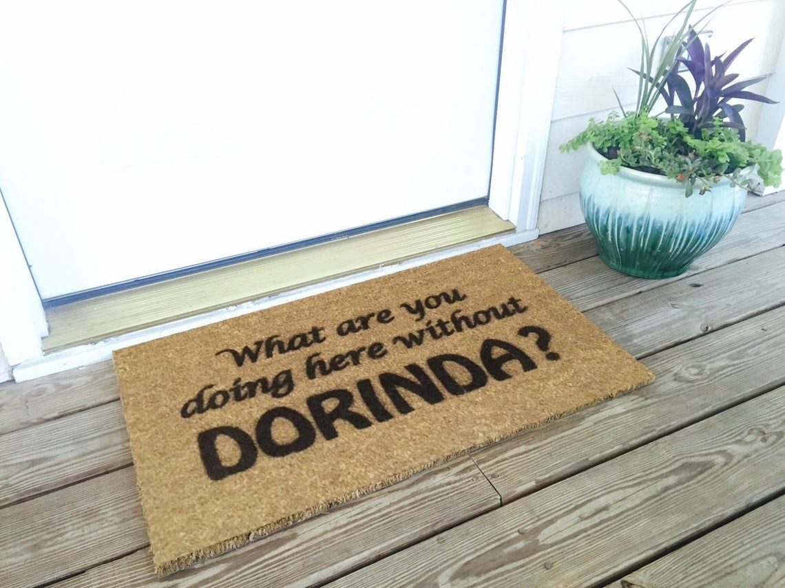 """front door with brown welcome mat that says """"what are you doing here without dorinda"""" from the real housewives of new york"""