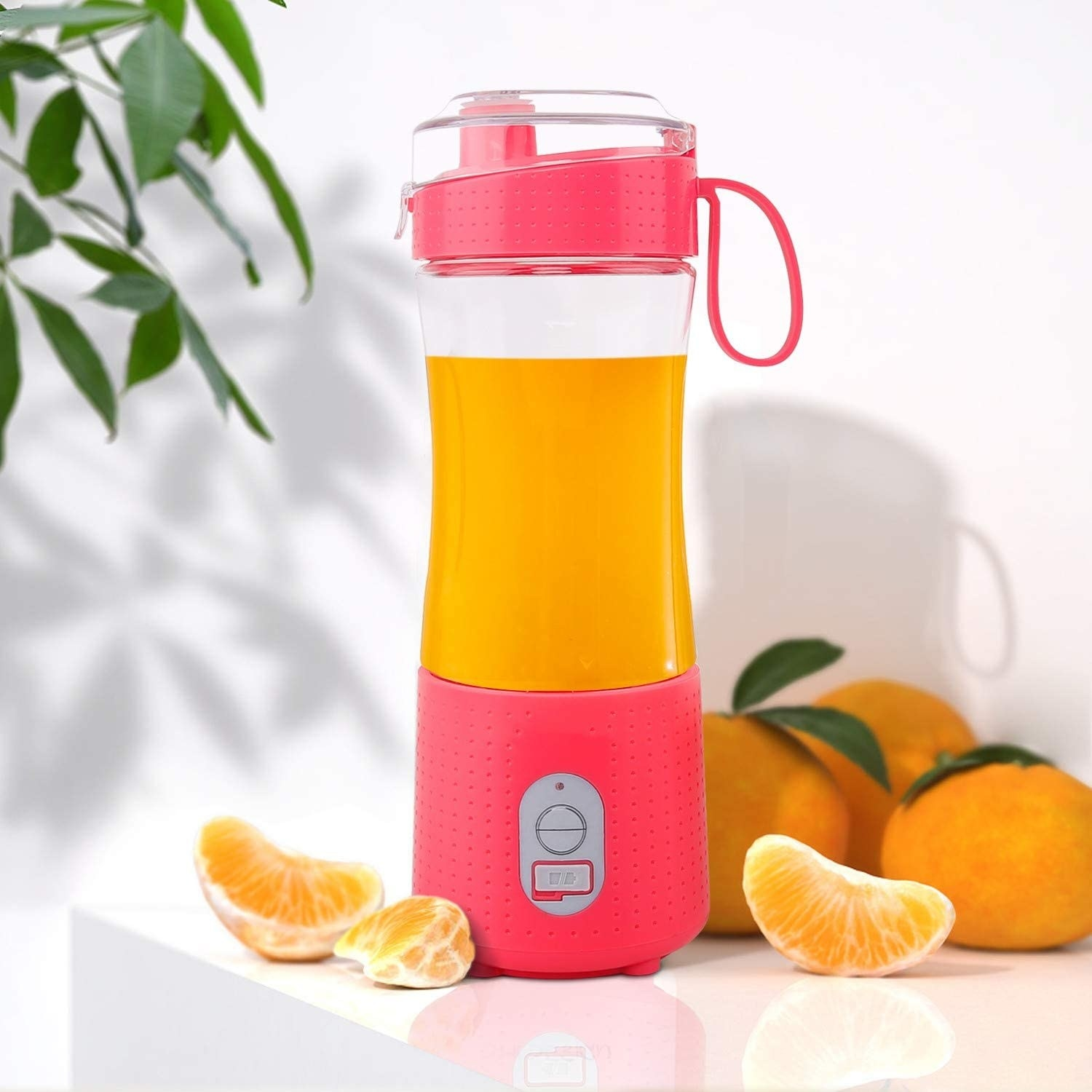 A handheld blender filled with fresh orange juice next to wedges of clementines