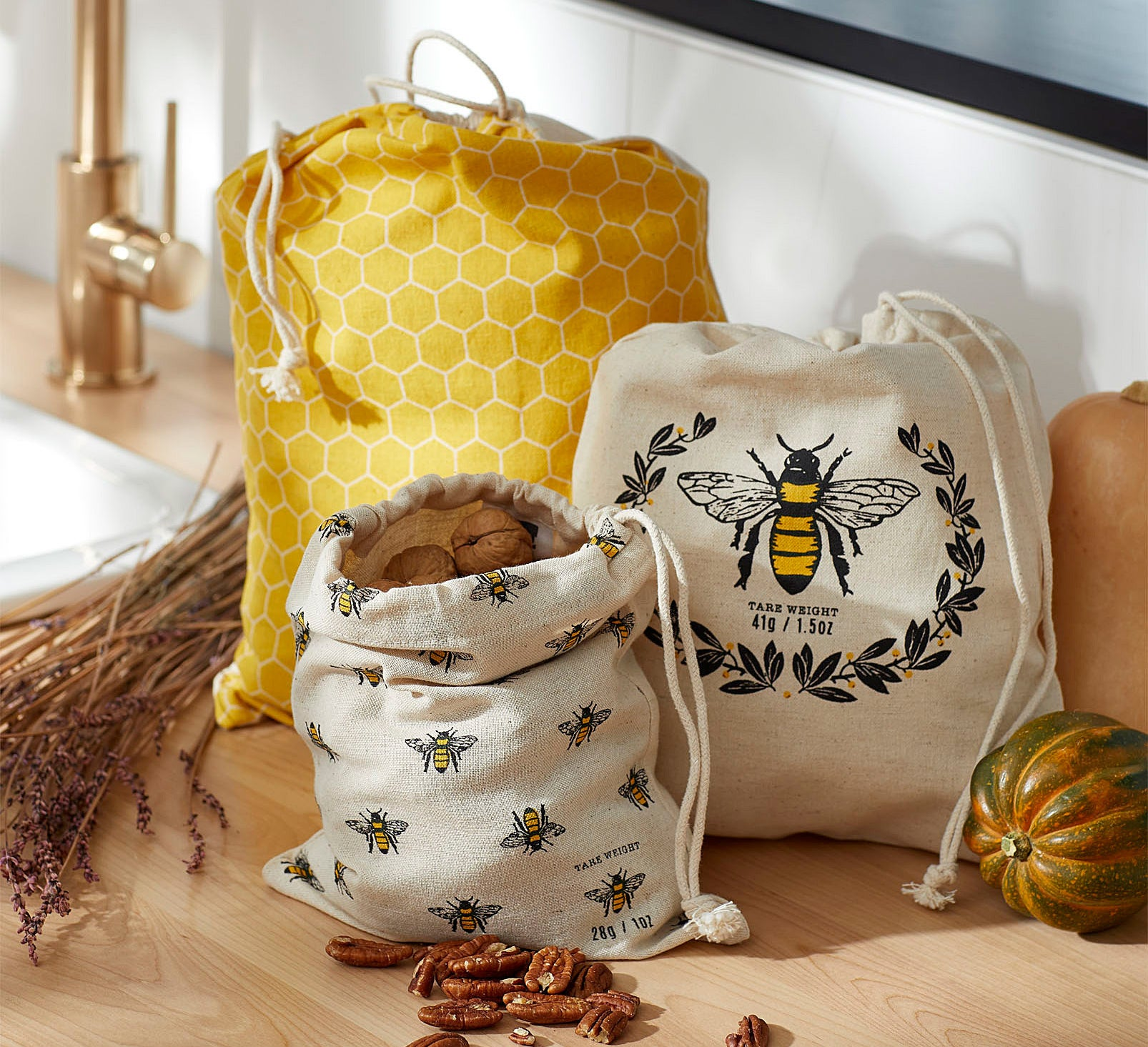 Three bee-themed bags with drawstrings on a counter