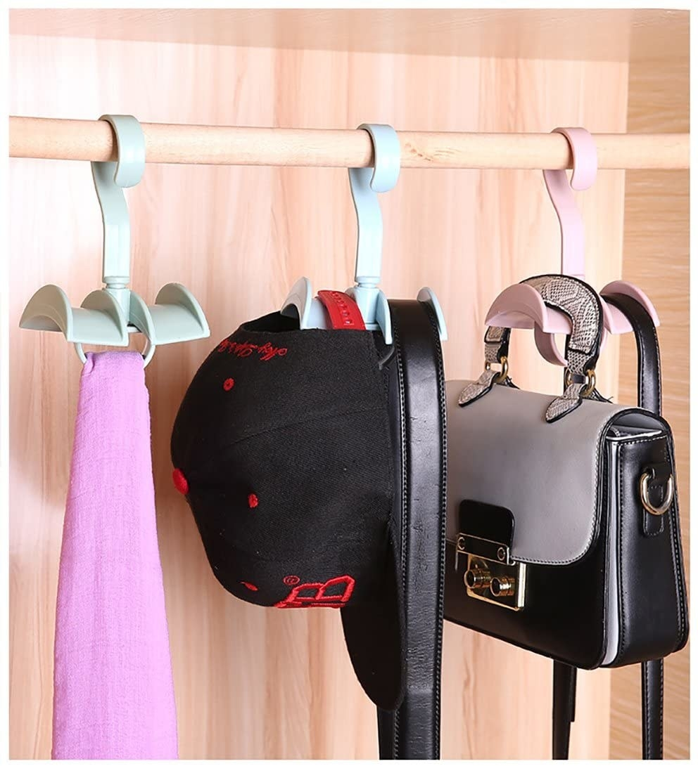 A set of three rotating hooks laden with hats, scarves, and purses