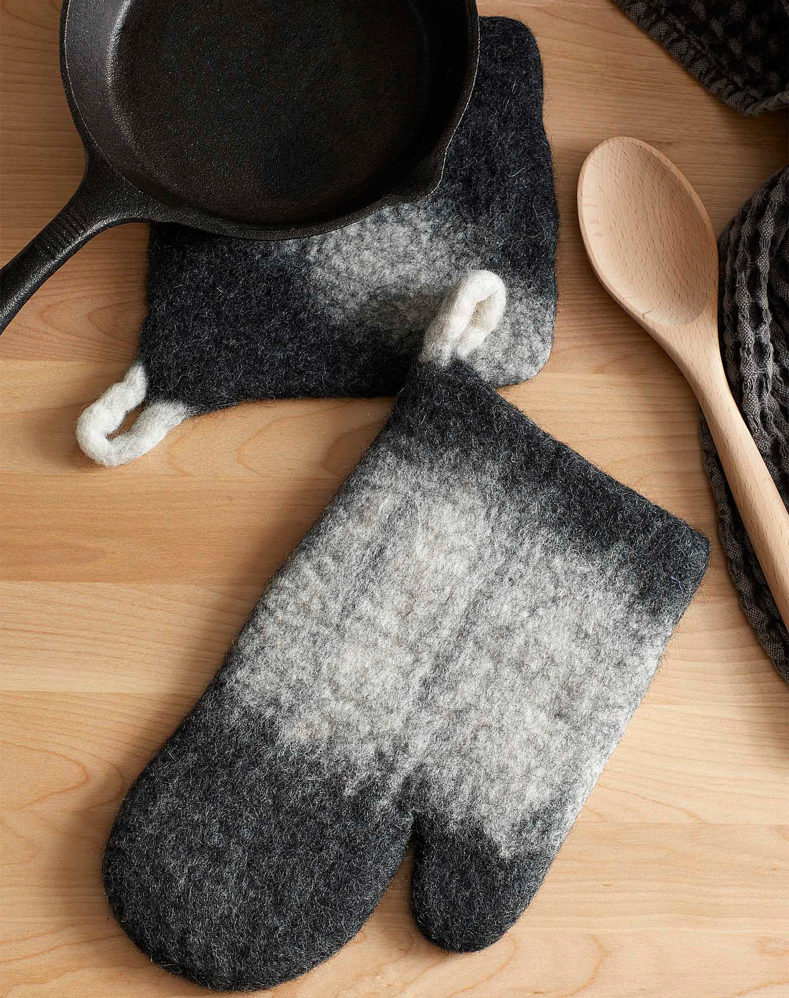 A pan next to the wooly pot holder and mit on a table