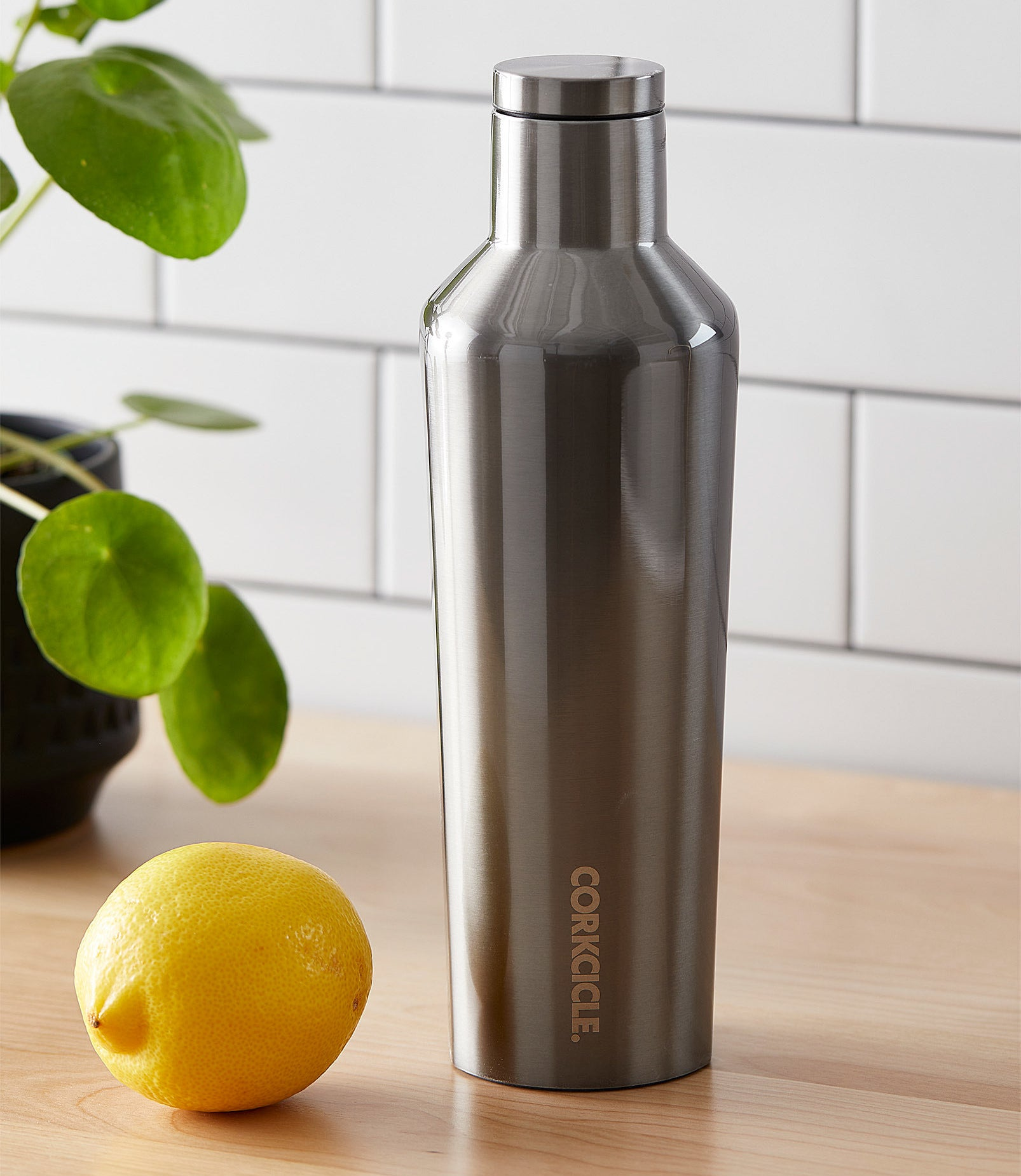 A metallic insulated bottle on a counter next to a lemon