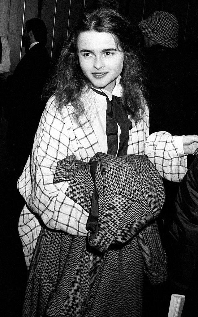 Helena Bonham Carter at 19 years old with long, frizzy hair, wearing an over-sized plaid shirt, and an over-sized coat