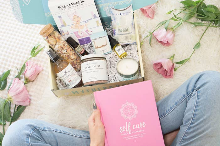 "A model holding a book titled ""Self care"" siting in front of a box filled with various wellness products"