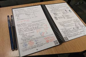 Reviewer pic of the notebook open on a desk with notes neatly written on either side and two pens sitting next to it