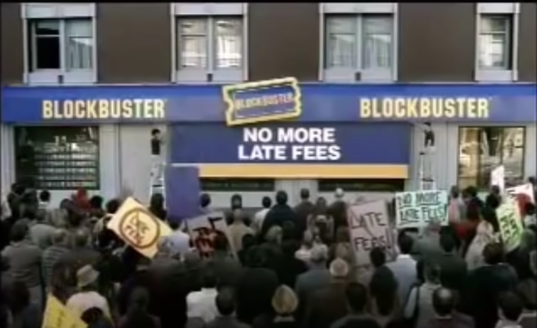 """A screenshot of crowd in front of Blockbuster store with a sign that is being put up that says """"No More Late Fees"""""""