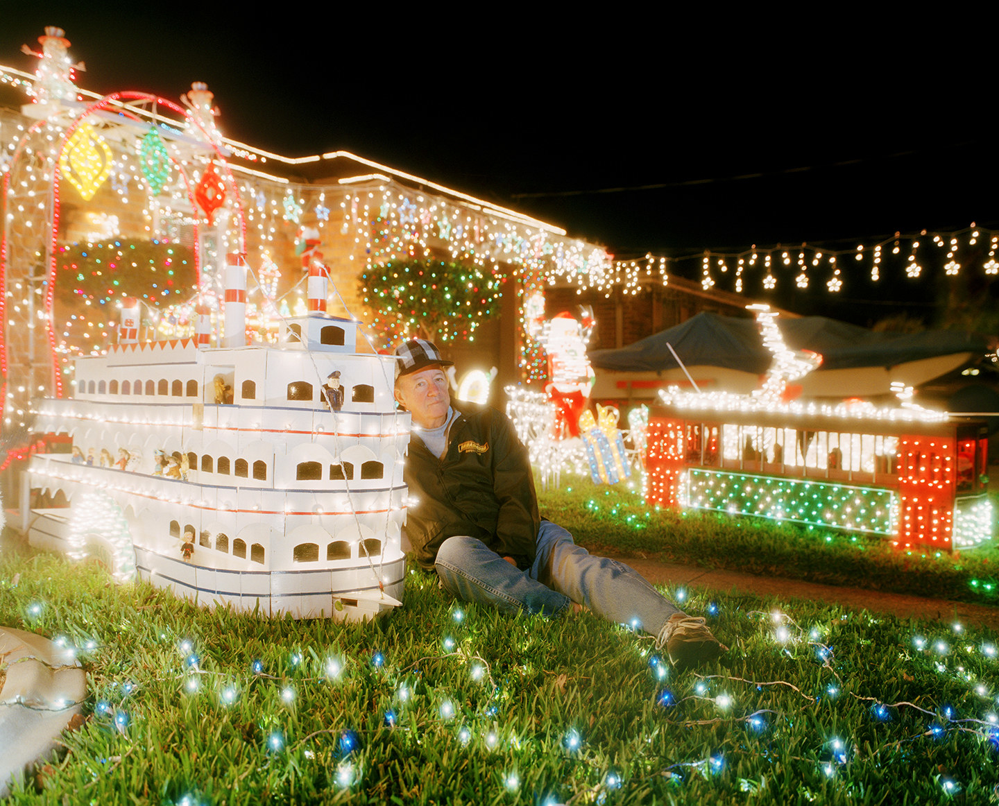 A man and a few models of riverboats, on the lawn of a house covered in Christmas lights