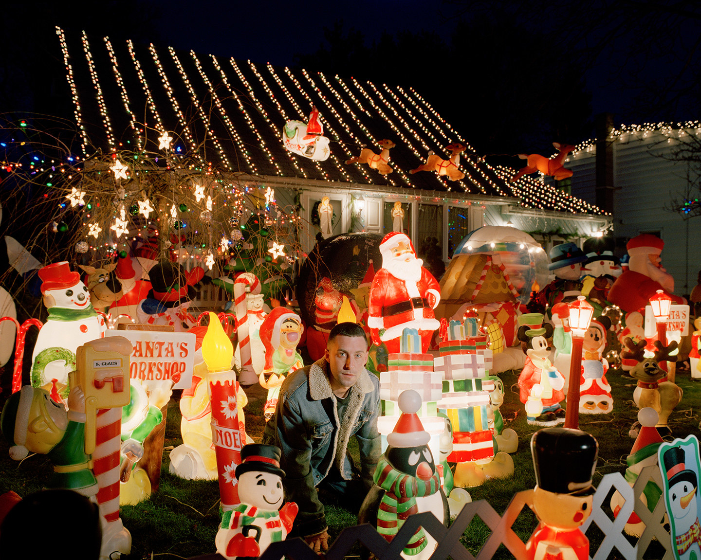 A man surrounded by Christmas ornaments on a lawn in front of a house