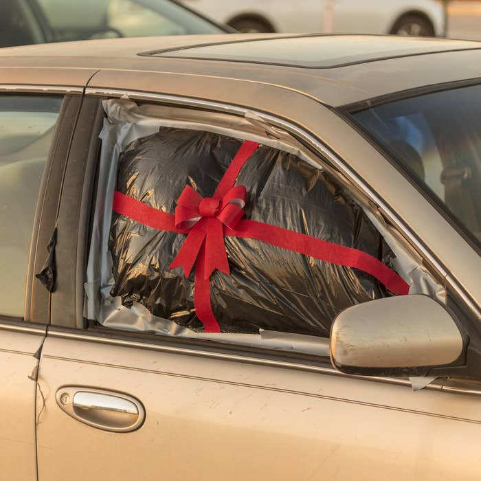 A passenger-side car window is covered in a garbage bag, duct-taped to the vehicle, and decorated with a ribbon and bow