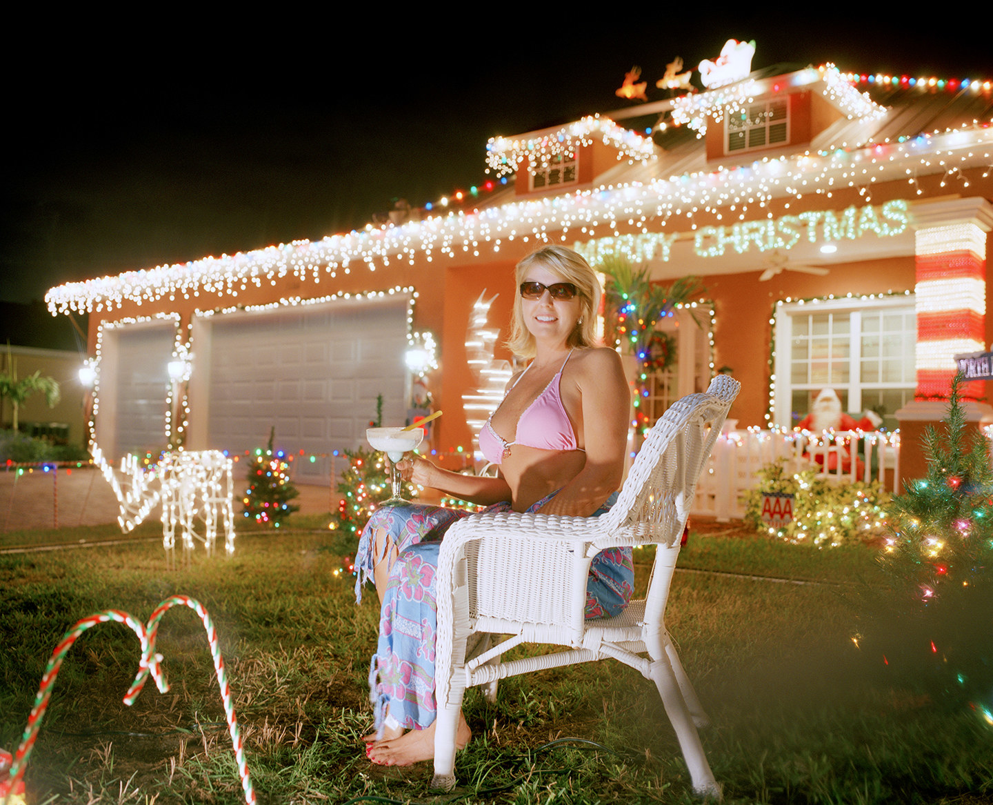 A woman in a bikini top and sarong on the lawn of her house, covered with lights