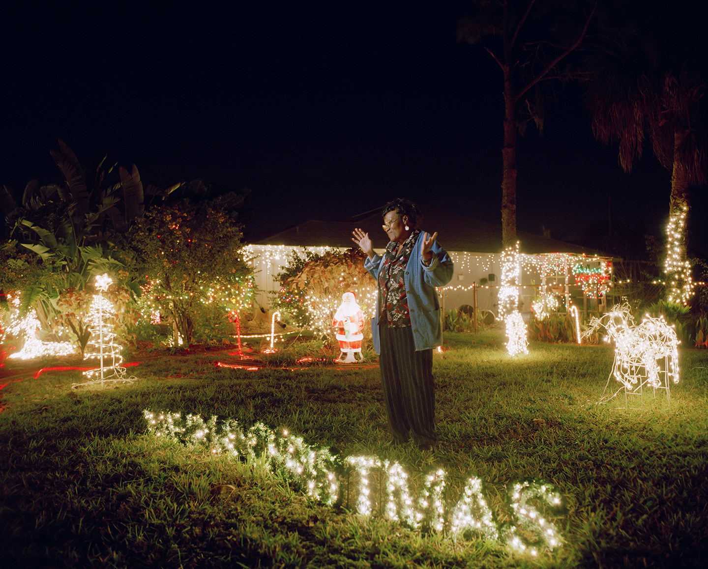 A woman on her lawn surrounded by Christmas ornaments