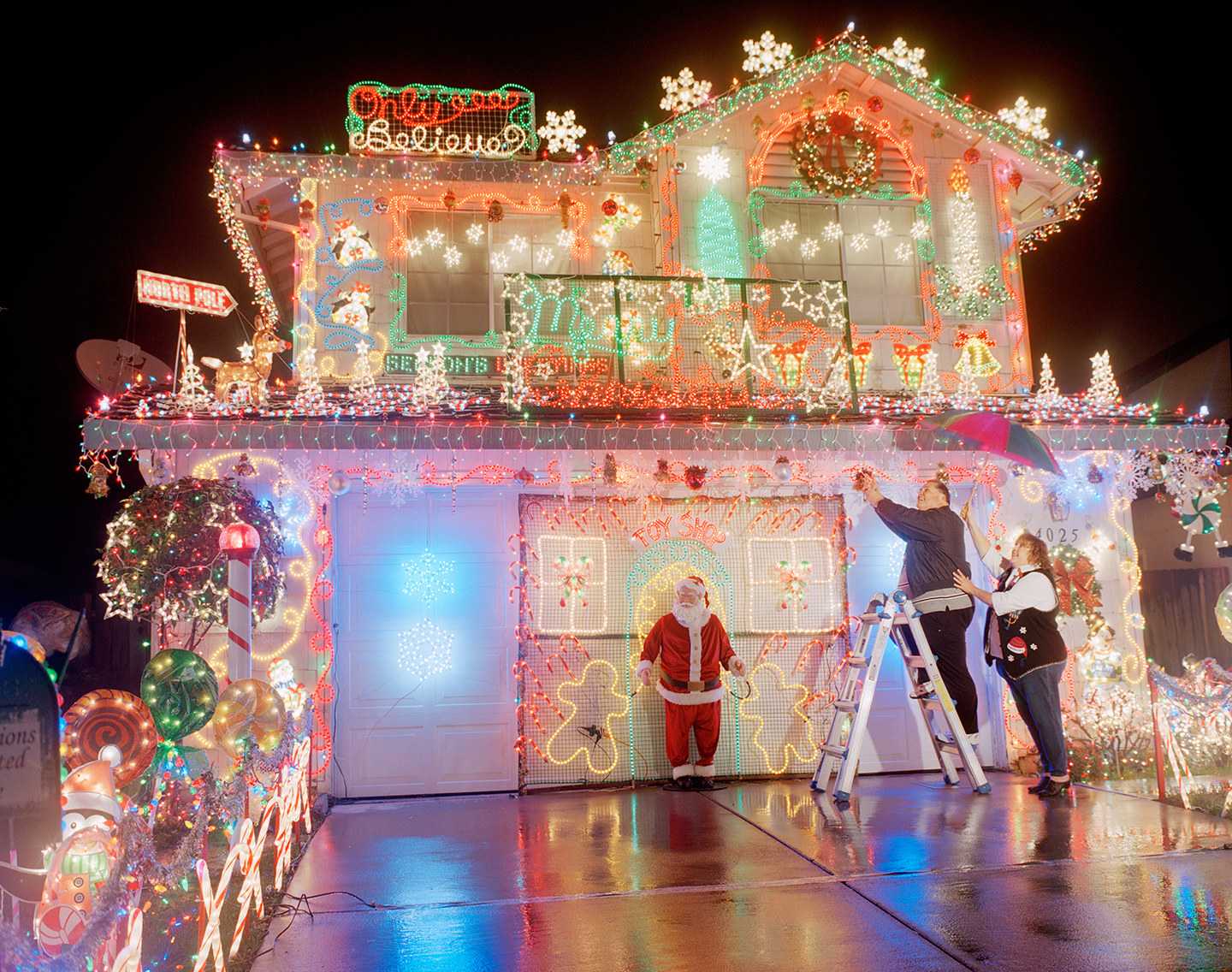 A man on a ladder adjusting Christmas lights on a house, with a woman supporting him, and a model of Santa