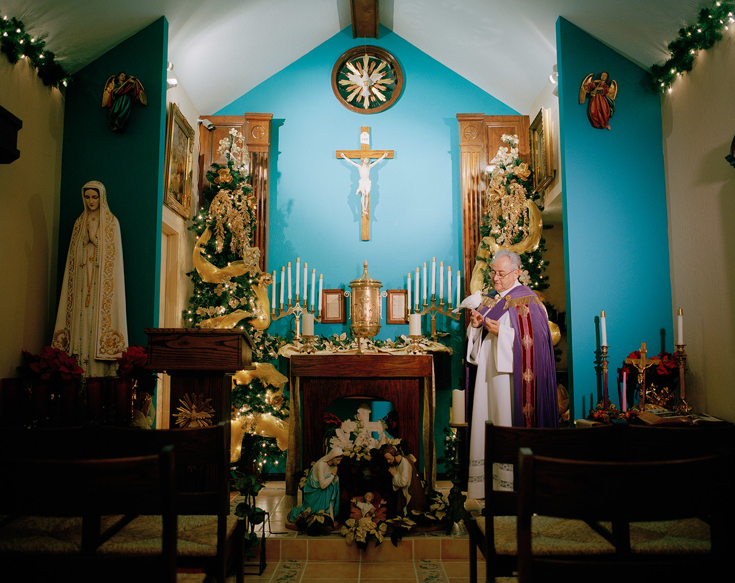 A man dressed as a priest in a small shrine inside a home
