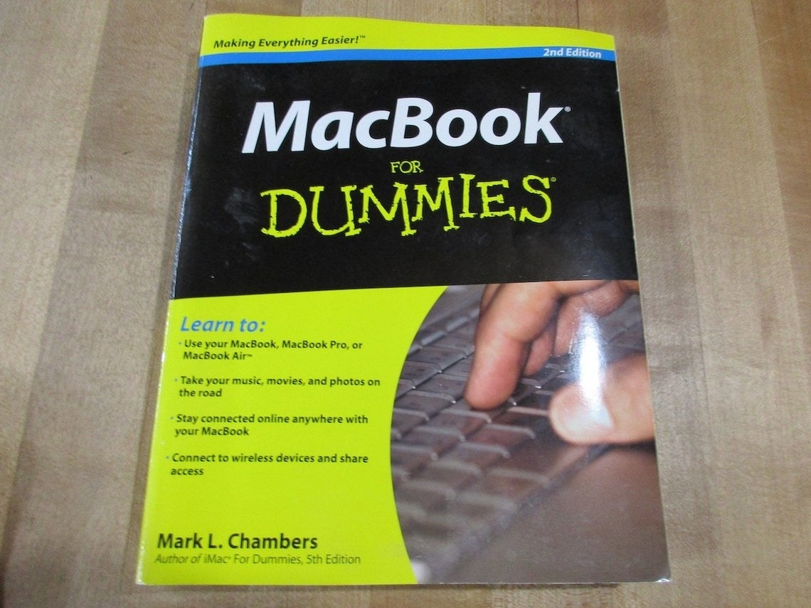 """A """"MacBook for Dummies"""" book featuring a hand typing on a keyboard on the cover"""