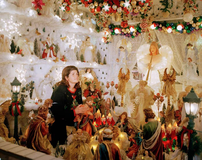 A woman sitting in a large nativity display indoors