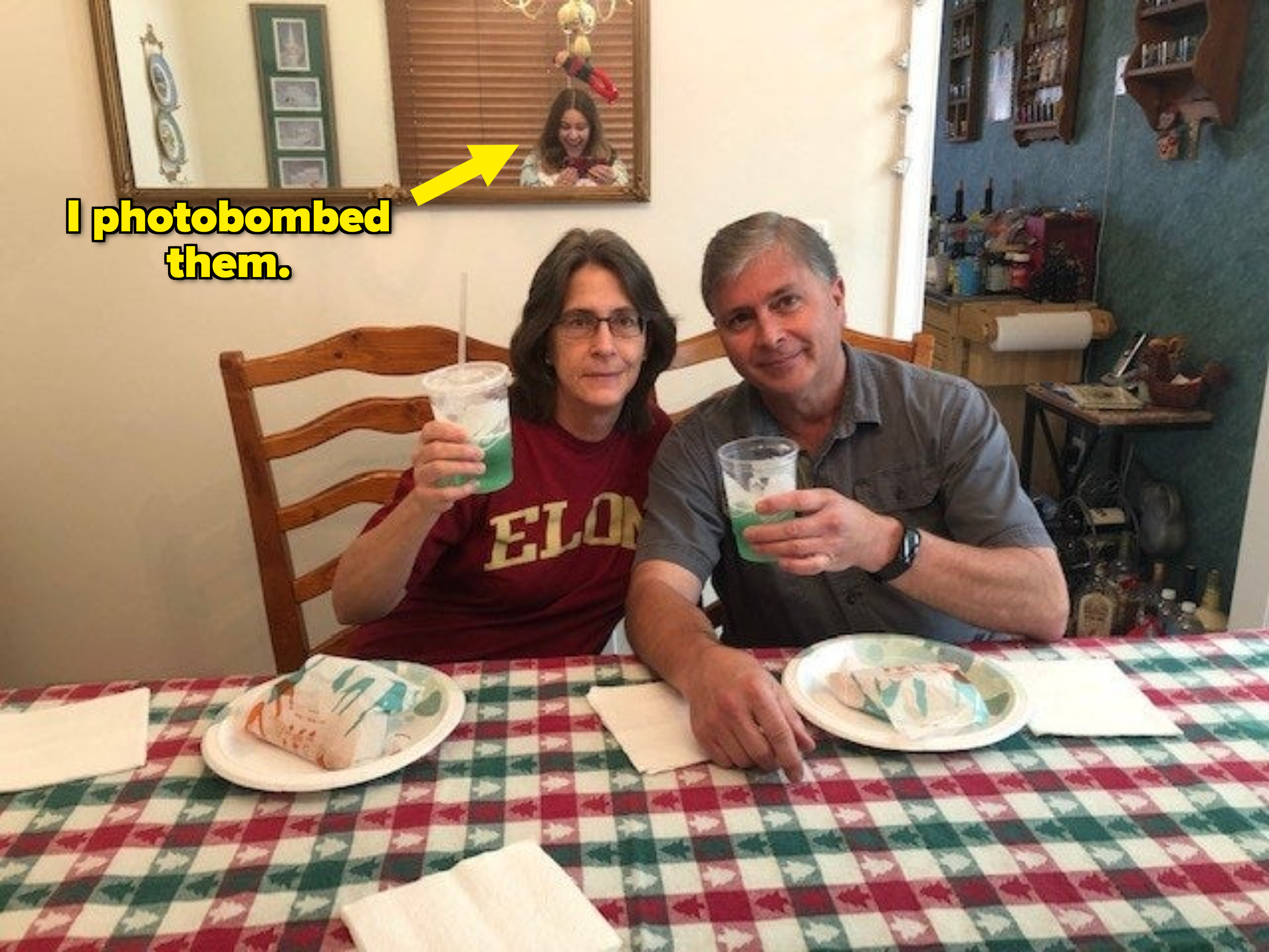 Parents holding Taco Bell drinks while sitting together at a table