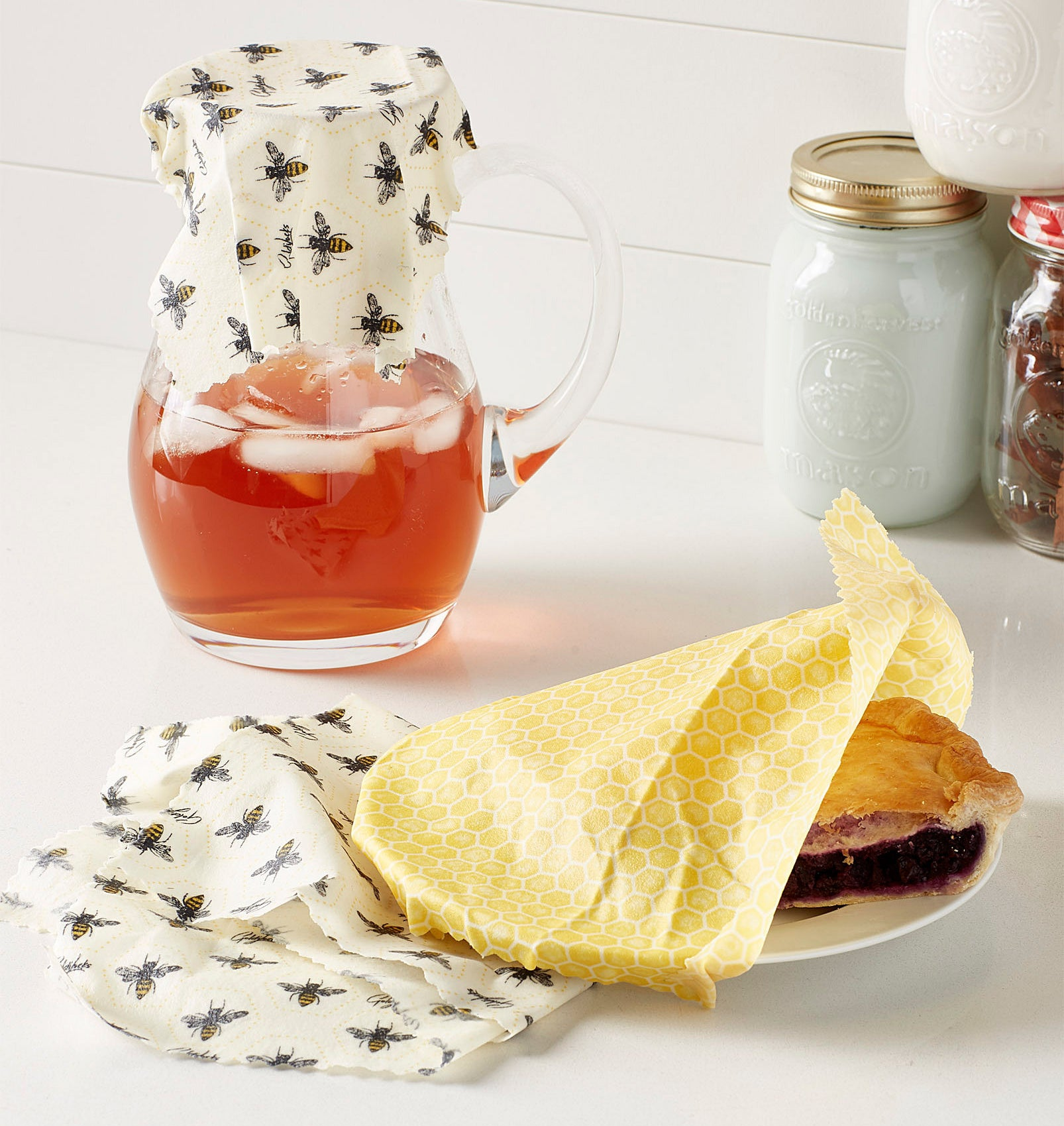 Three wraps on a counter covering a pitcher of juice and a pie
