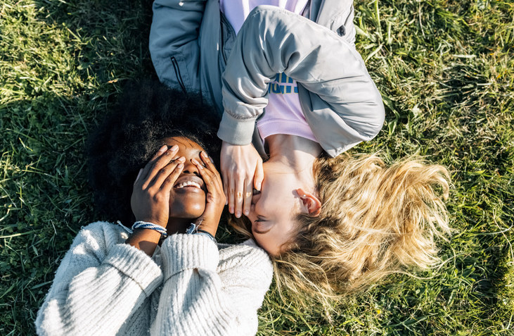 two girls lying in the grass with their heads next to each other laughing