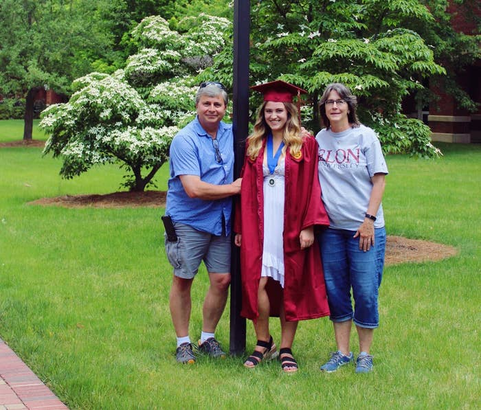 Family posing for graduation photos outside