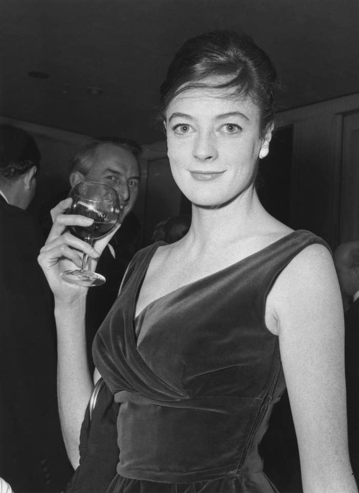 Maggie in a velvet dress holding a glass of wine