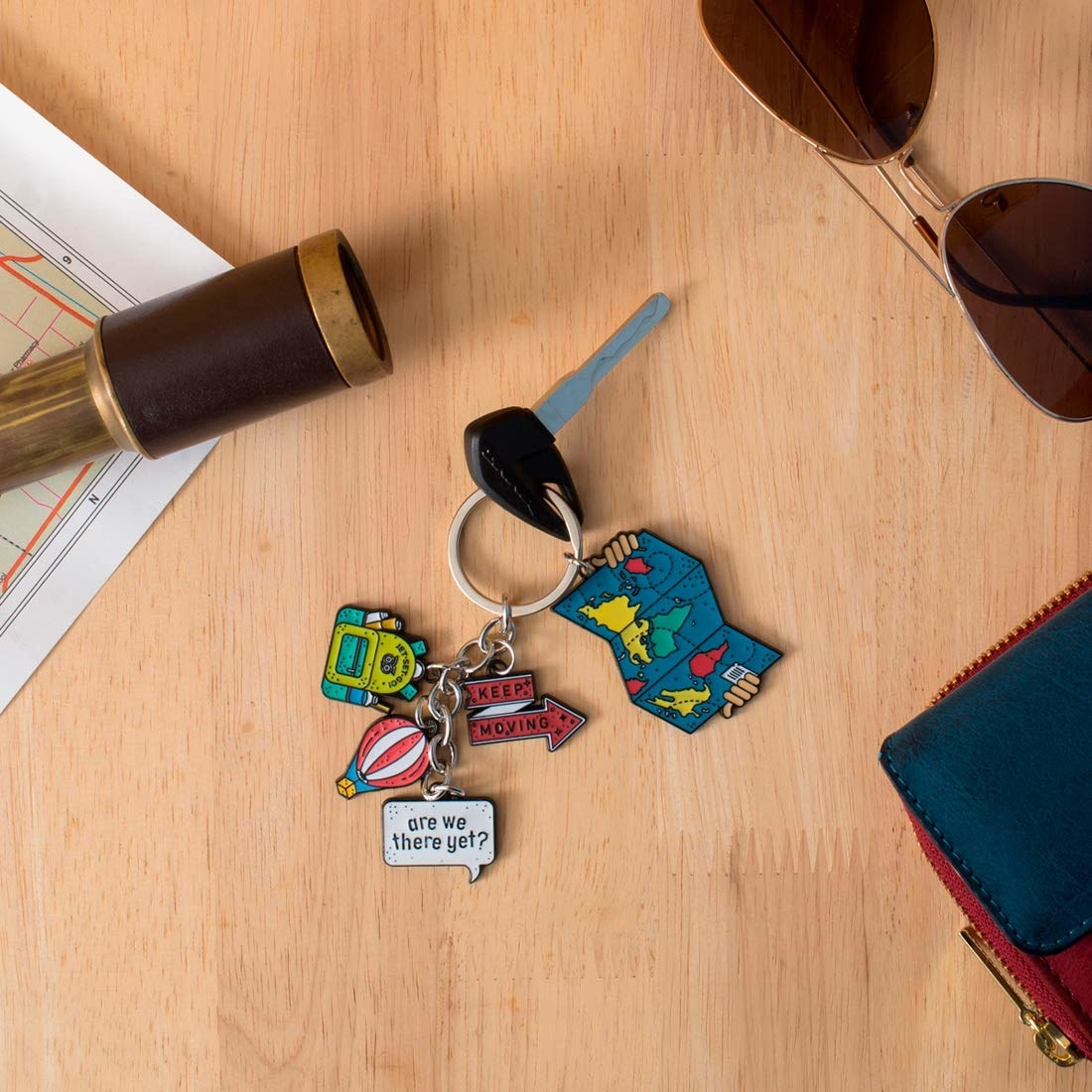 A key chain with backpack, hot air balloon, map, Keep Moving, Are We There Yet charms.