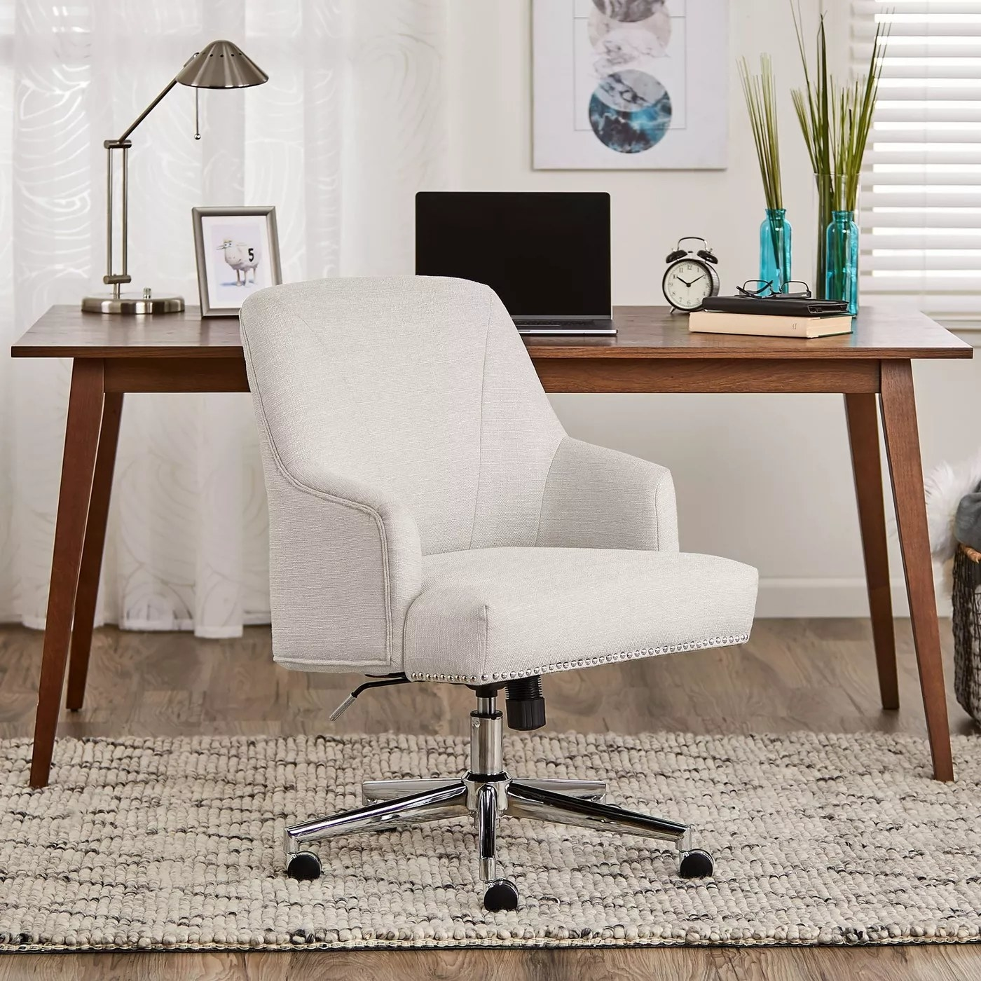 The ivory office chair with studs around the rim of the chair in a home office