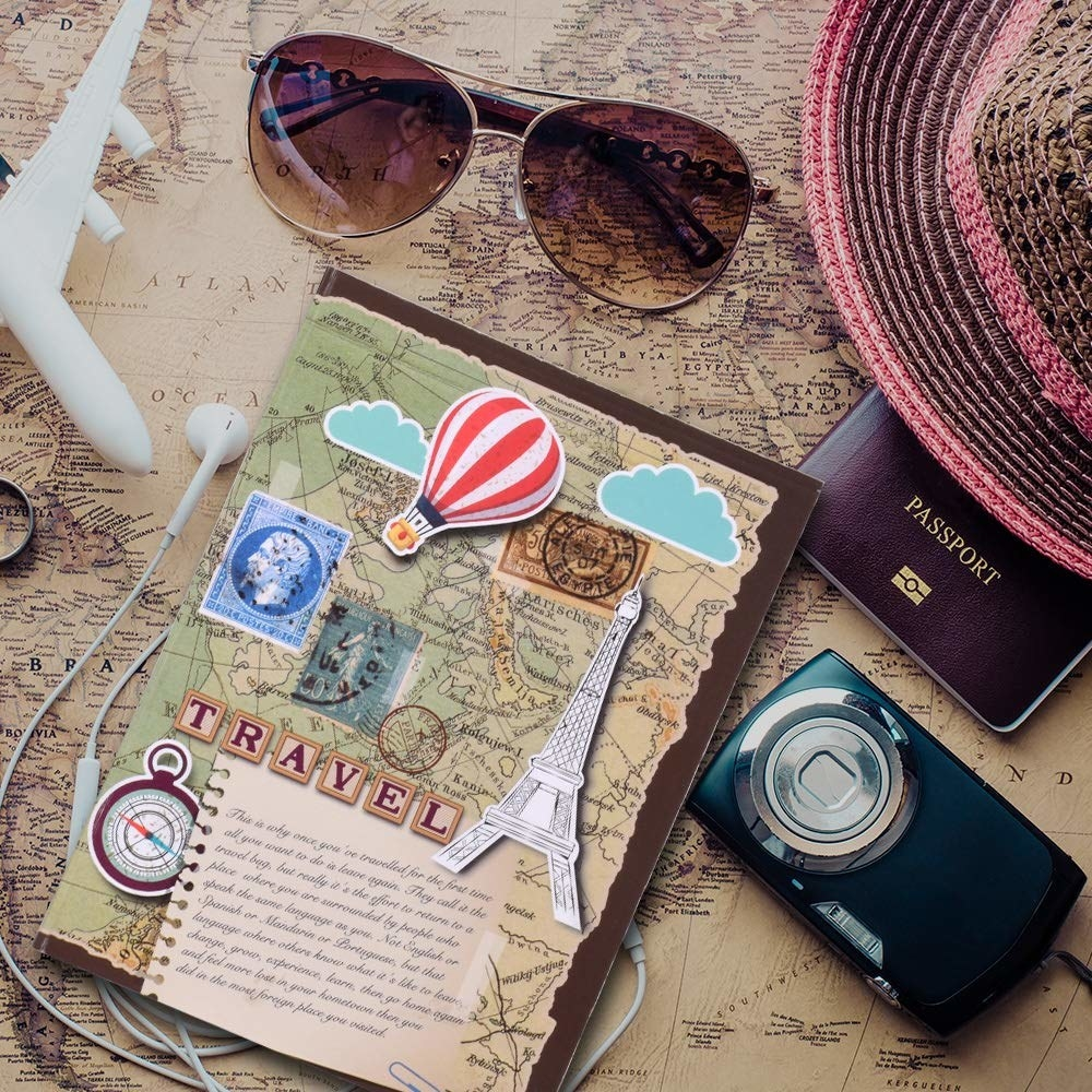 A travel journal with a map design on the cover. There is a camera, passport cover, pair of sunglasses, and earphones near it.