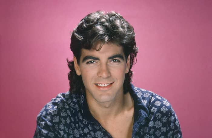 Head shot of George in a printed blue shirt with a pink background
