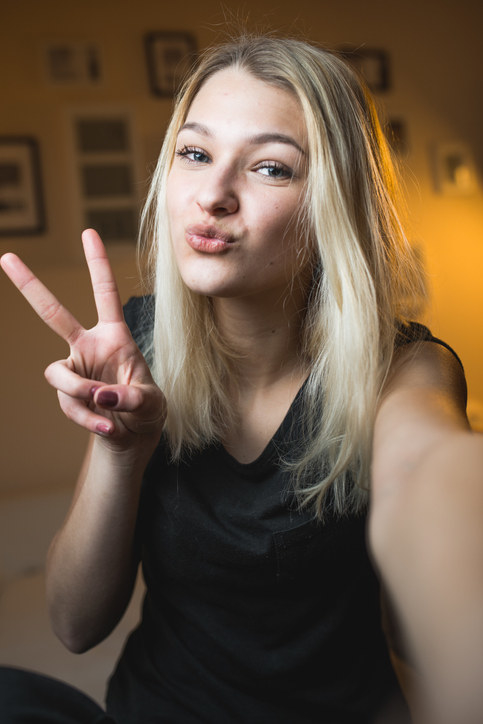 a girl taking a selfie with a peace sign and duck face