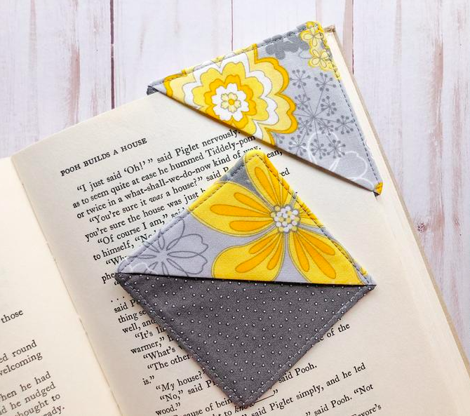 A cute fabric square bookmark that fits over the corner of an open book