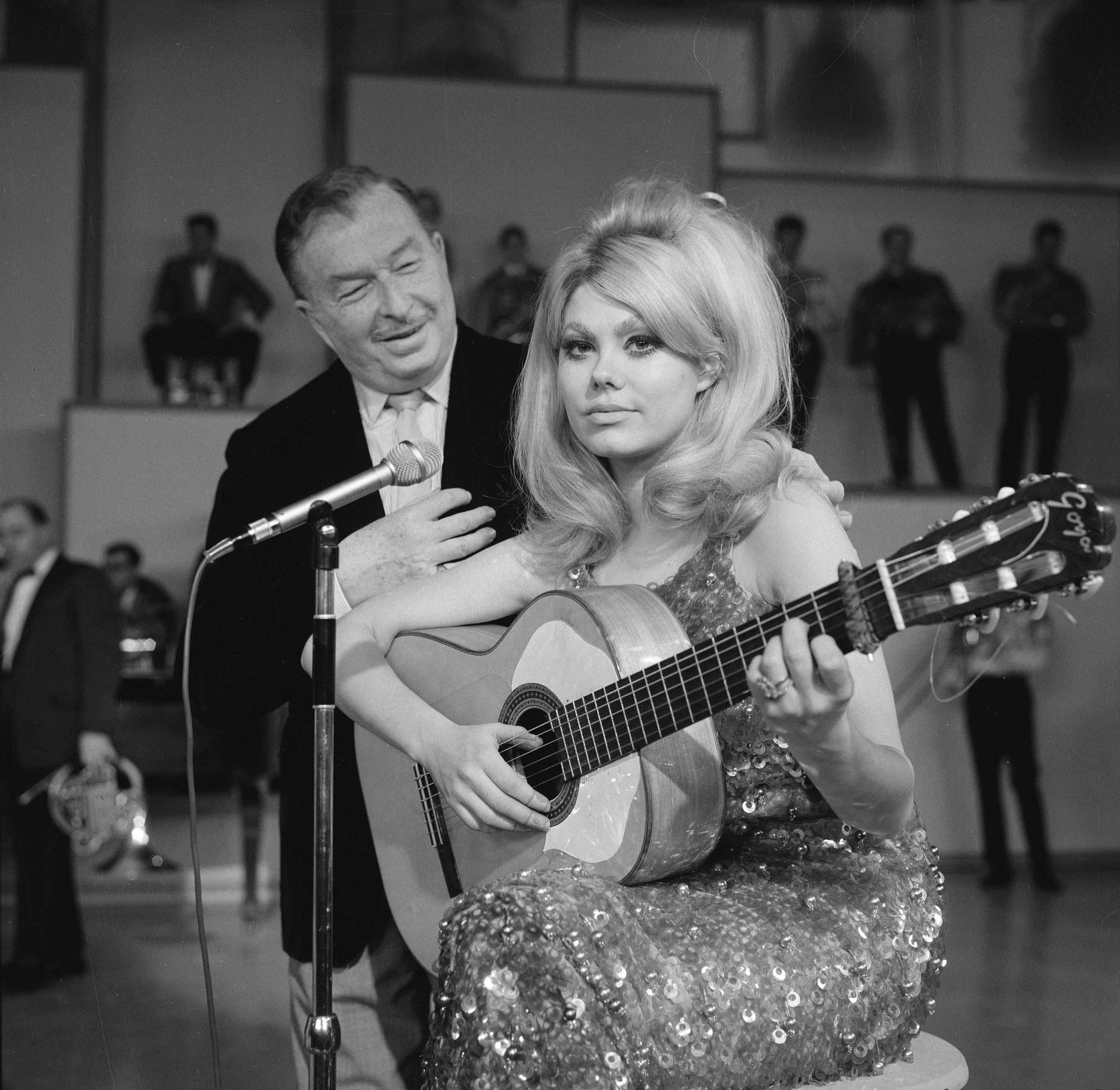 Charo on a stage sitting on a stool and in front of microphone while holding a guitar