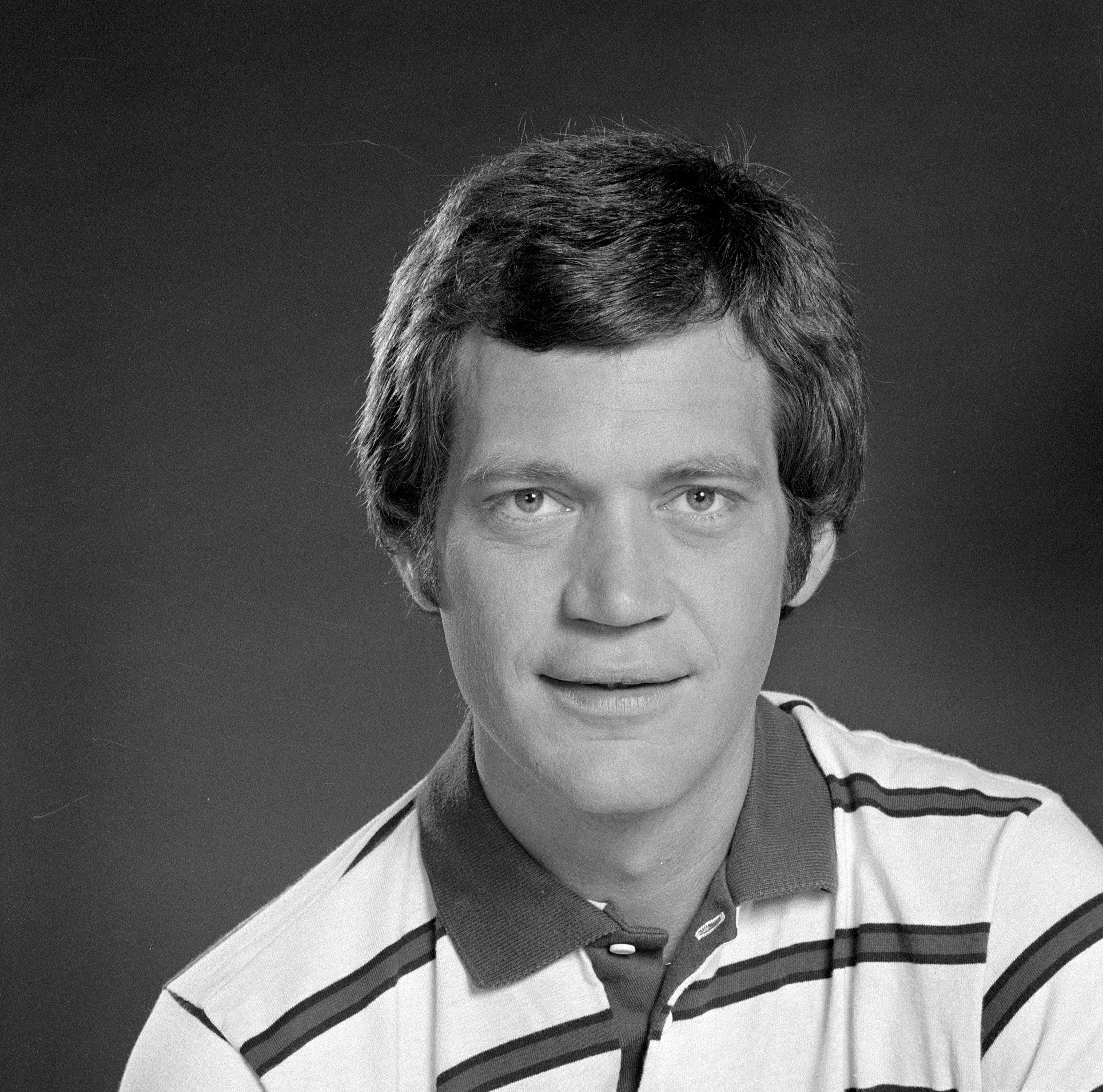 Publicity photo of David where he is wearing a striped polo