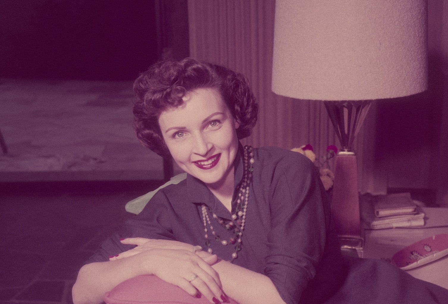 Betty in a navy blue dress leaning on a couch