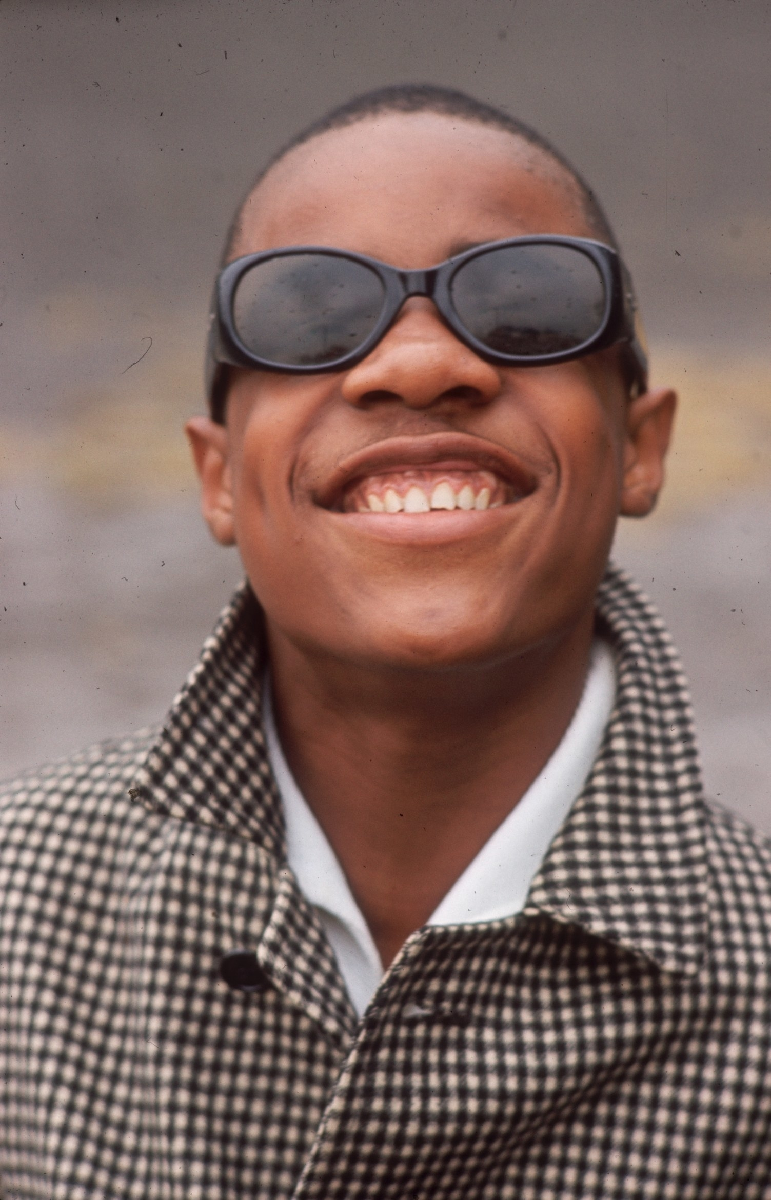 Steve smiling wearing cat-style sunglasses and a houndstooth coat