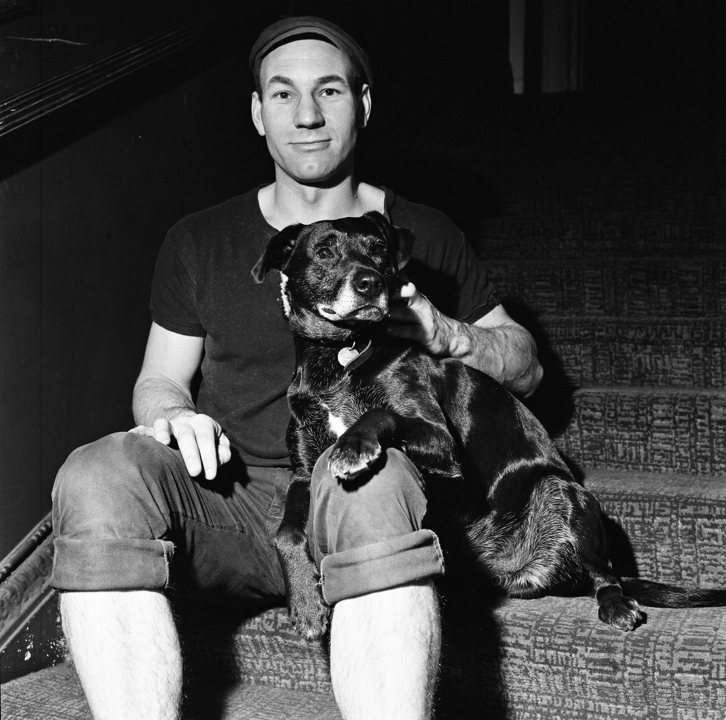 Patrick sitting on some stairs with a black dog on his lap