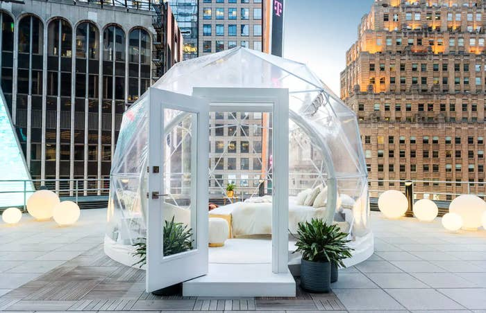 A clear dome with a bed on a NYC rooftop