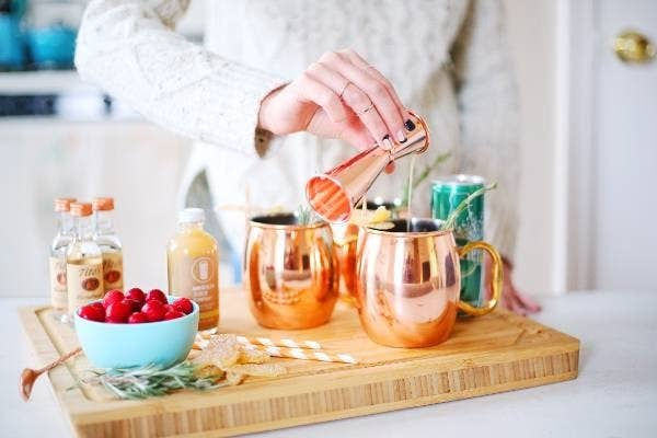 A model pouring a shot into a copper mug surrounded by various cocktail ingredients