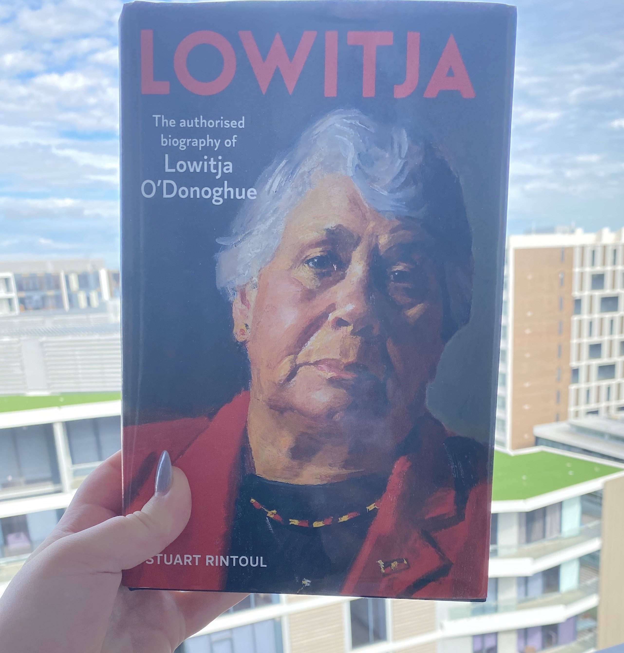 Person holding a book showing a portrait of Lowitja O'Donoghue