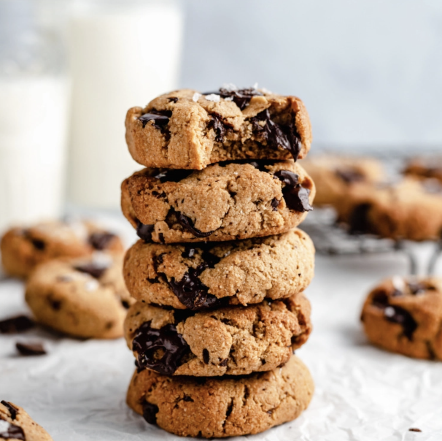 A stack of five small but nuggety chocolate chip cookies, topped with a sprinkle of salt