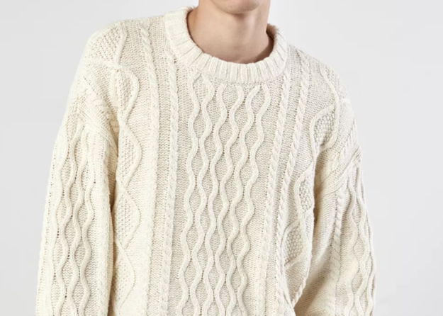 A thick, cable-knit sweater with a vertical swirly design down the front