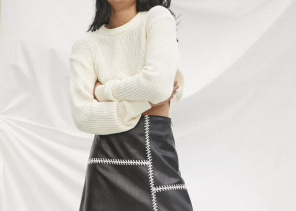 A delicate cropped sweater and a leather mini skirt with thick stitching