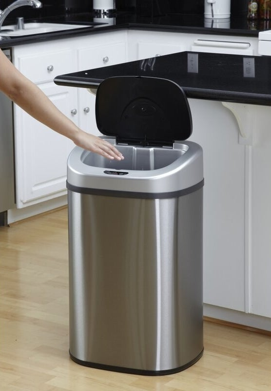 The trash can, which is made of brushed steel, with a plastic flip lid